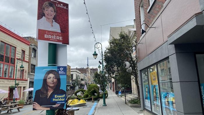 لافتتان انتخابيتان مُعلّقتان على عمود في الشارع.