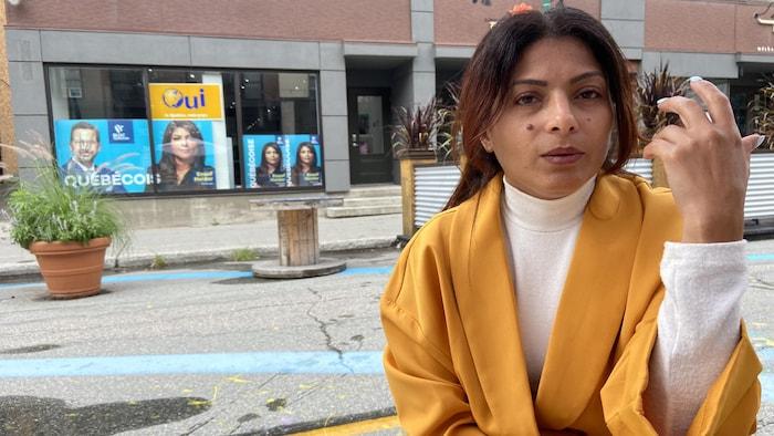 امرأة جالسة على طاولة في الشارع وهي تتحدث رافعًة يدها.
