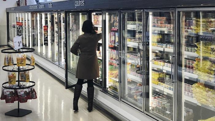 Une femme se sert dans le réfrigérateur d'un magasin d'alimentation.