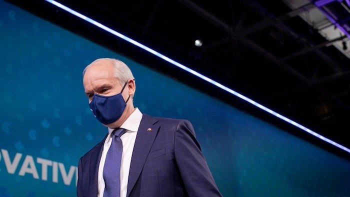 Conservative Leader Erin O'Toole, wearing a mask, leaves the stage.