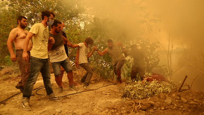 2021年夏季希腊遭受了 30 年来最严重的热浪袭击,2021年 8 月 8 日,人们在 l'île d'Evia 与野火抗争,这个岛距离雅典 200 公里。