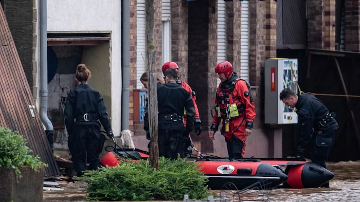Lifeguards and police divers with an inflatable boat go into a flooded courtyard in Erftstadt, Germany on Friday. Heavy rains caused mudslides and flooding in the western part of Germany.
