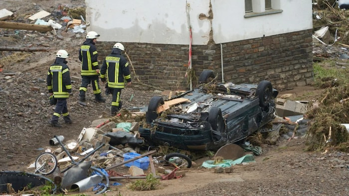 Firefighters walk past a destroyed car in the community of Schuld, Germany on Friday. Heavy rains caused mudslides and flooding in the western part of Germany.