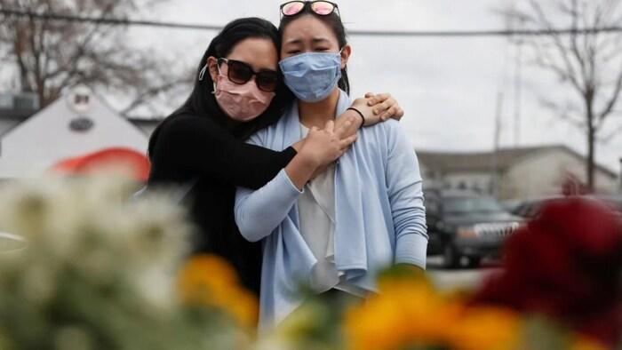 "Two people embracing looking at a flower-filled ""Memorial"" in Atlanta."