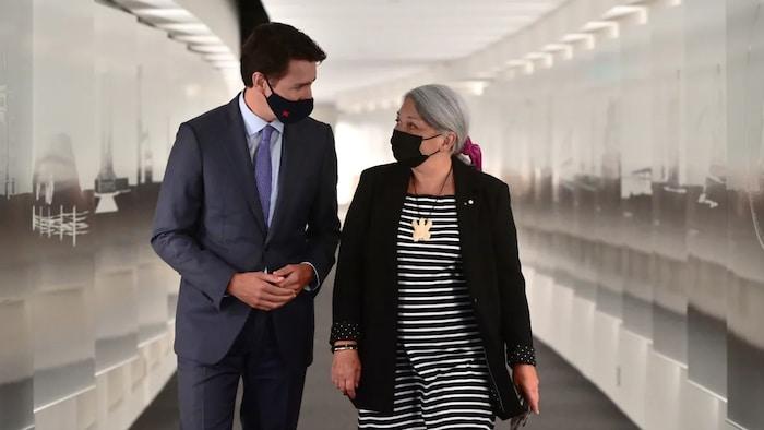 جوستان ترودو وماري سايمون يمشيان في رواق المتحف الكندي للتاريخ وهما يرتديان قناع الوجه للحماية من كوفيد 19 ويتحدّثان مع بعضهما البعض.