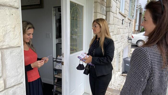 امرأتان تتحدثان إلى امرأة ثالثة تقف على عتبة منزلها.