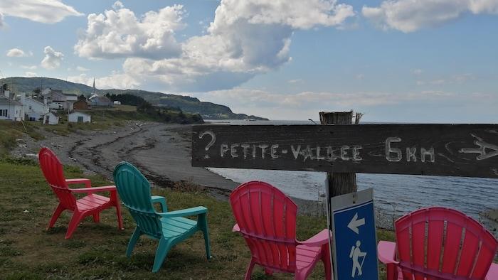 Une pancarte sur laquelle on peut lire : « Petite-Vallée, 5 km » devant des chaises installées face au fleuve.