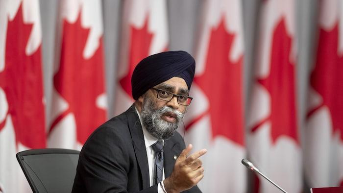 وزير الدفاع الكندي هارجيت سجّان متحدثاً في مؤتمر صحفي في أوتاوا وتبدو خلفه أعلام كندية.