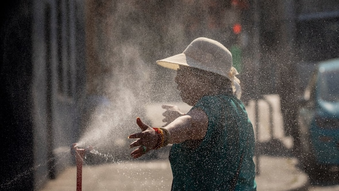 A person uses a misting station in Vancouver on Monday. (Ben Nelms/CBC)