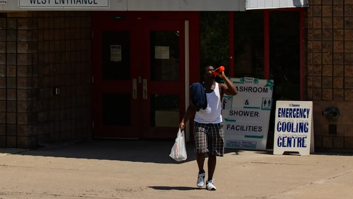 A man leaves a community centre in Toronto during a heat wave earlier this month. Some cities have been opening cooling centres during heat waves for people who do not have access to air conditioning.