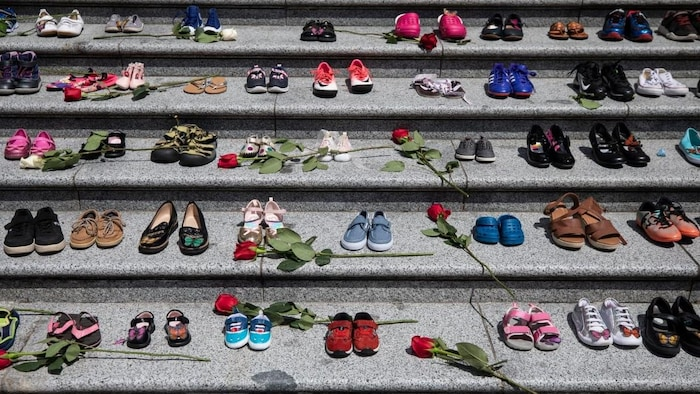 Zapatos infantiles y rosas en una escalera.