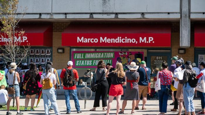 Un grupo de manifestantes se reunió frente a la oficina del Ministro de Inmigración Marco Mendicino en Toronto después de la muerte de tres trabajadores migrantes que contrajeron COVID-19 para exigir un estatus migratorio completo para todos los residentes no permanentes en Canadá con el fin de ampliar los beneficios de la asistencia sanitaria, el apoyo de ingresos de emergencia y las protecciones laborales, el sábado 4 de julio de 2020.