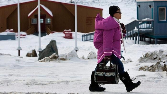 Une femme portant un parka traditionnel marche sur la rue en hiver.