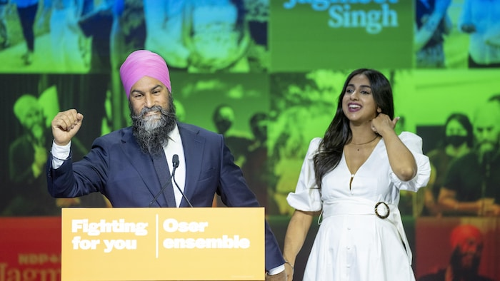 Singh and wife stand on stage with NDP posters backdrop. The couple is smiling and celebrating.