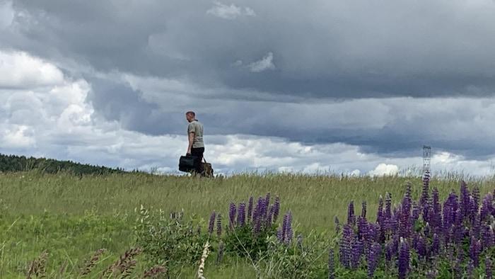 Un homme marche dans un champ.