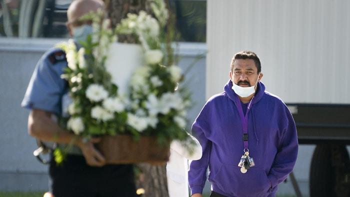 Carol Dubé regarde un agent de sécurité transporter des fleurs.