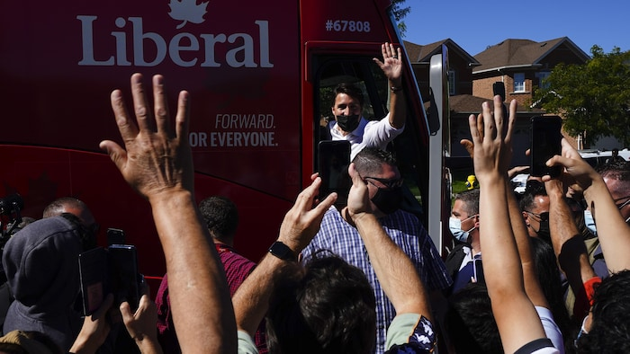 Justin Trudeau waves at crowd from the door of Liberal shuttlebus.