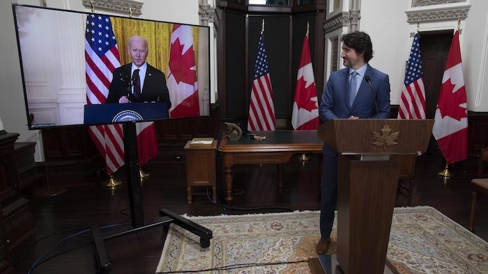 Justin Trudeau mira con una sonrisa al presidente estadounidense Joe Biden, visto en una pantalla, durante una cumbre virtual entre ambos hombres.