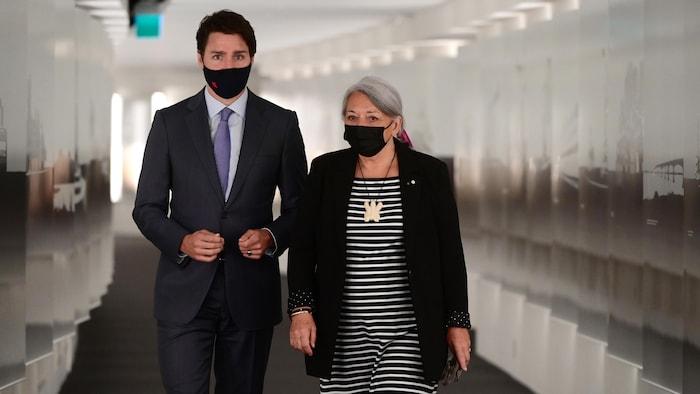 Justin Trudeau et Mary Simon marchent côte à côte en portant un masque.