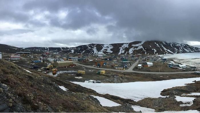 Des habitations en bas d'une montagne avec des traces de neige.