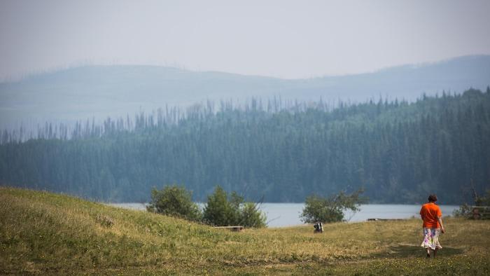 Una persona camina cerca de un lago.