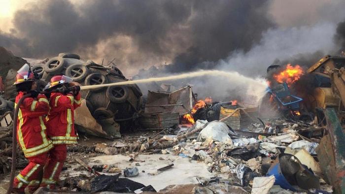 عناصر إطفاء يكافحون النيران المشتعلة في مرفأ بيروت.