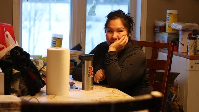 Une femme qui se tient la tête sur une table de cuisine encombrée.