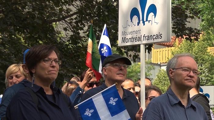 Grupo de personas con la bandera de Quebec y un afiche con la flor de la provincia.