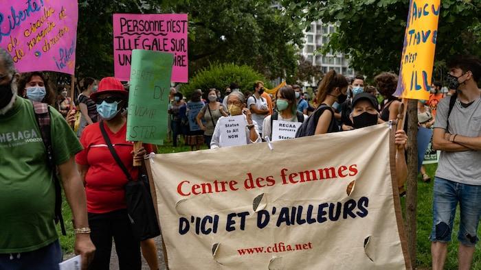 Manfiestantes sostienen una pancarta.