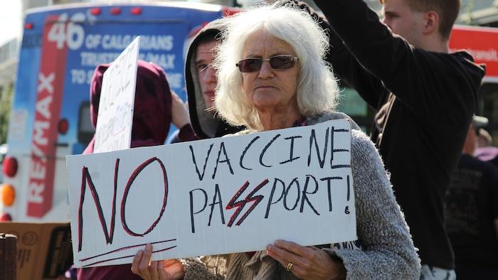 سيّدة تحمل لافتة معارِضة لِجواز التطعيم.