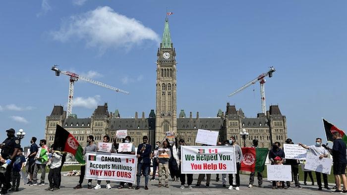 متظاهرون يرفعون لافتات أمام هضبة البرلمان في أوتاوا.