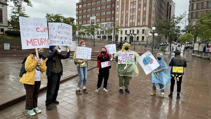 Des manifestants tenant des pancartes.