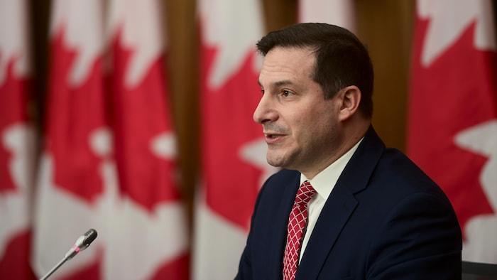 وزير الهجرة واللاجئين والمواطَنة الكندي ماركو منديتشينو متحدثاً في مؤتمر صحفي في أوتاوا وتبدو خلفه أعلام كندية.