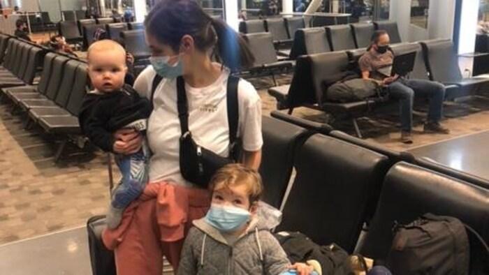 一位母亲带着两个孩子在机场。