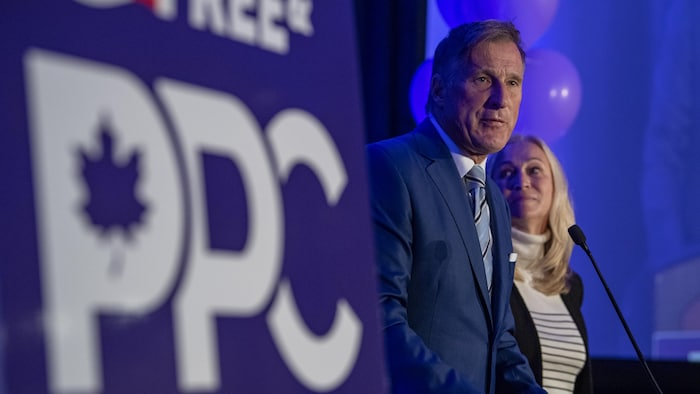 Maxime Bernier stands next to his party's banner with his wife, in front of microphone.