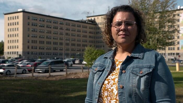 ميلاني بيروه، ممرضة في مستشفى جولييت، ونراها واقفة في الخارج أمام مبنى المستشفى الظاهر في عمق الصورة.