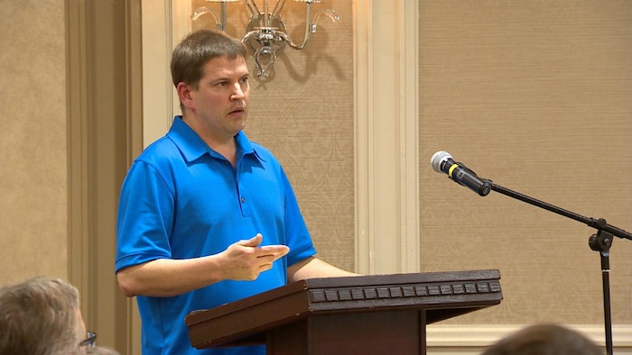 Un homme parle à un podium