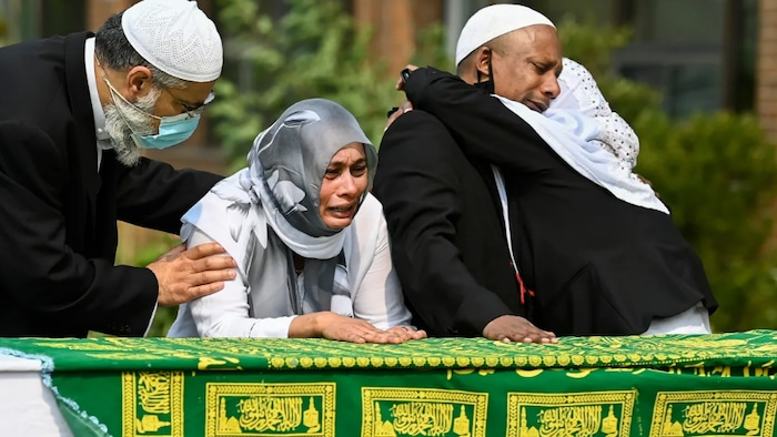 Bebe Zafis, second from left, and family members react at her father's casket during the funeral of Mohamed-Aslim Zafis in Toronto on Sept. 16, 2020. Police say Zafis was fatally stabbed while he sat outside a mosque to control entry to the building in order to comply with public health protocols.