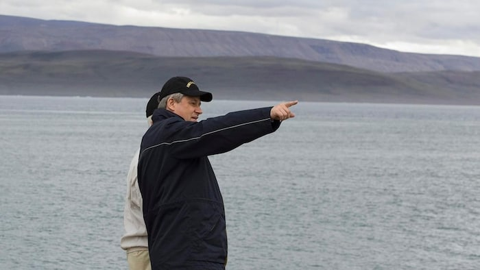 Stephen Harper with another individual pointing to the horizon on the shoreline in Nunavut.
