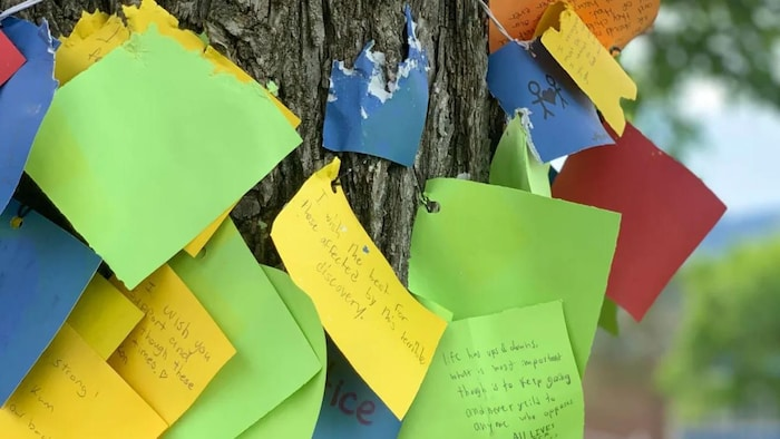 Messages written on small pieces of paper are taped to the trees in front of the Kamloops residence.
