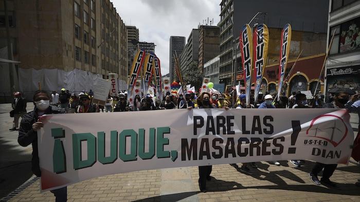 """Manifestantes sostienen una pancarta con un mensaje que dice en español: """"Duque, pare las masacres"""", dirigido al presidente de Colombia, Iván Duque, mientras marchan hacia la Plaza de Bolívar en Bogotá, Colombia, el miércoles 12 de mayo de 2021."""