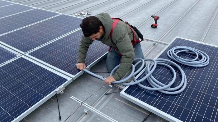 Un trabajador instala paneles solares.