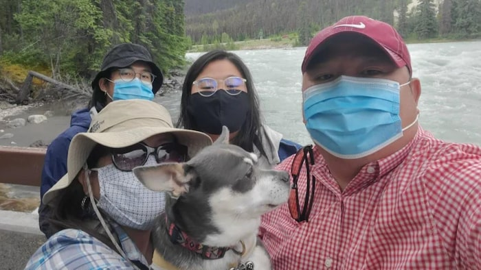 Photo of a family in the open air with their dog, wearing protective masks.