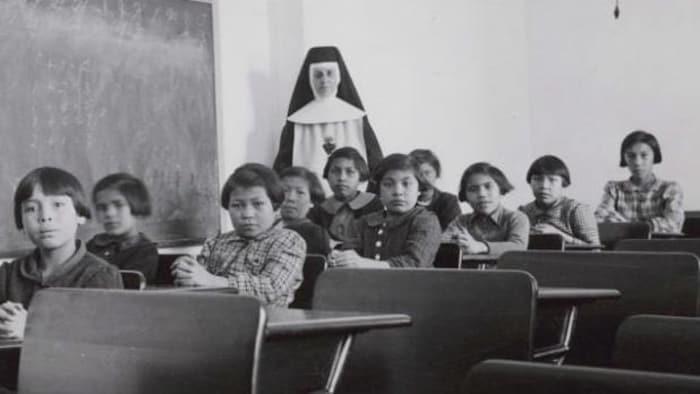 Des étudiants et une religieuse posent dans une salle de classe du pensionnat Cross Lake.
