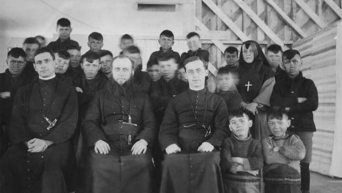 Plusieurs dizaines d'enfants autochtones posent debout. À l'avant de la photo, trois prêtres sont assis.