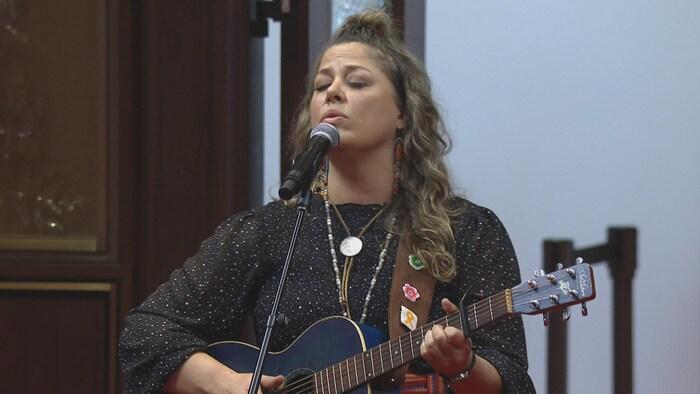 Una mujer canta ante el micrófono con una guitarra.