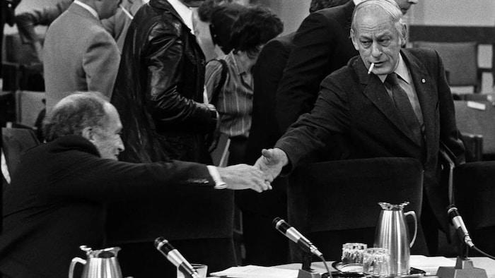 El primer ministro Pierre Trudeau se estira para estrechar la mano del primer ministro de Quebec René Lévesque.