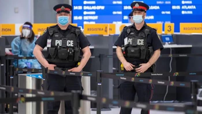 شرطيّان وعاملو صحّة في مركز الكشف عن كوفيد-19 في مطار تورونتو الدولي