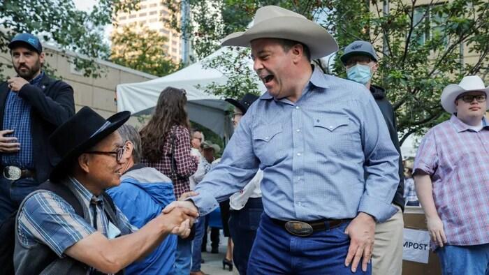Jason Kenney, sin máscara, da la mano a un visitantes en la Estampida de Calgary.