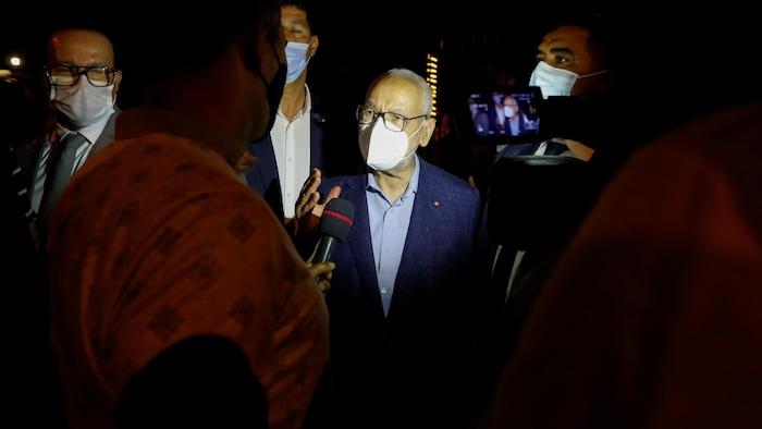 رئيس البرلمان التونسي، زعيم حركة ''النهضة''، راشد الغنّوشي متحدثاً إلى صحفي، ونراه واضعاً غطاء وجه واقياً من الفيروسات.